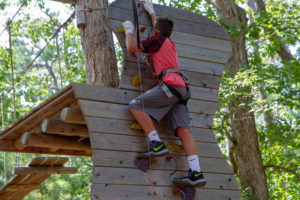 Climb a rock wall on the kids course at Tree to Tree Aerial Adventure Park
